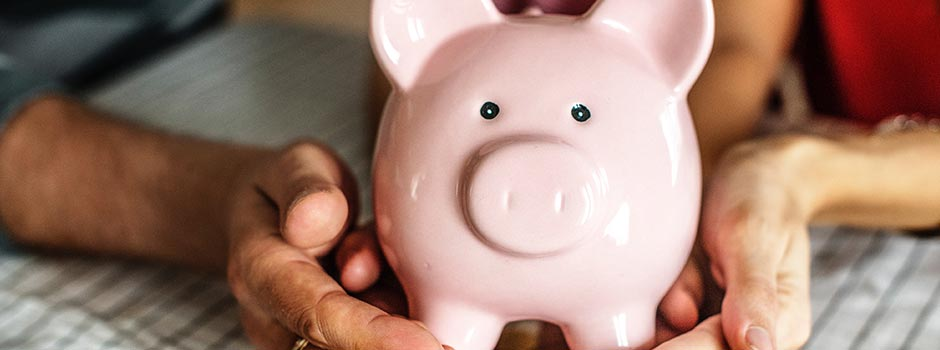 Close-up of a family holding a pink piggy bank.
