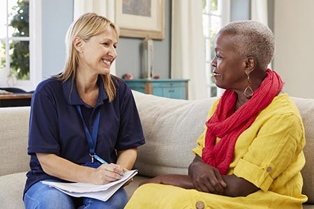 Social worker speaking with an older woman in her home.