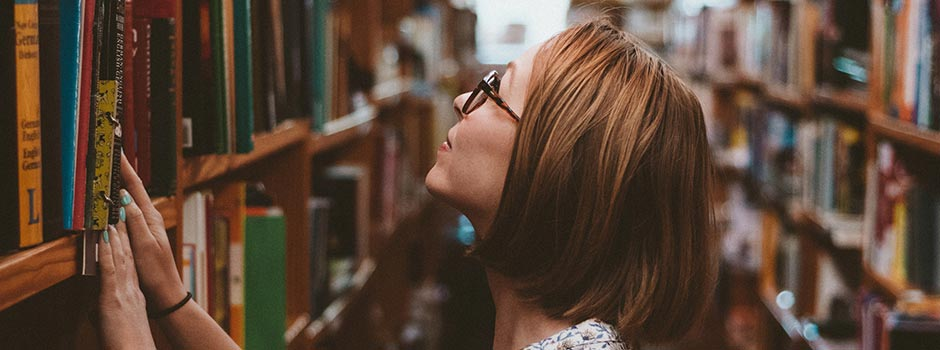 Photo of a woman looking at book in a library.