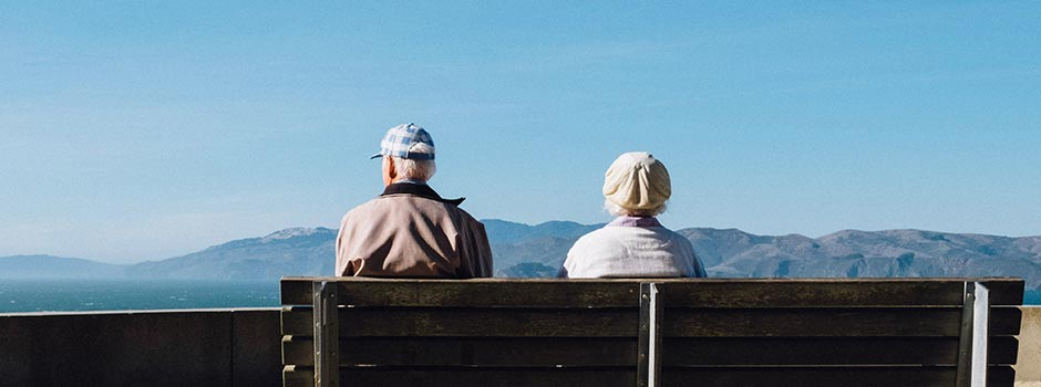 An older couple sits on a bench overlooking a park and mountain range.