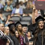 Graduate excited and holding diploma holder in the air