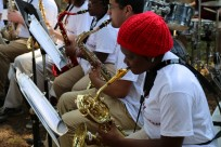woman in red hat playing sax with band