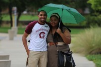 Two students under green umbrella