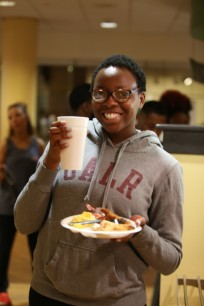 student smiling and eating pancake
