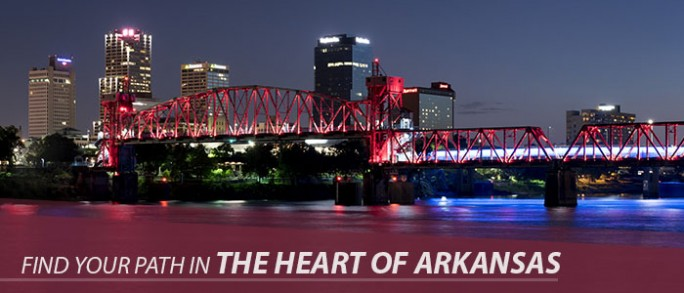 "An image of the junction bride downtown at night, with text that says, ""Find your path in the heart of Arkansas."""