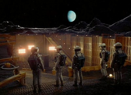 "Still image from movie ""2001: A Space Odyssey"" showing astronauts standing on lunar surface"